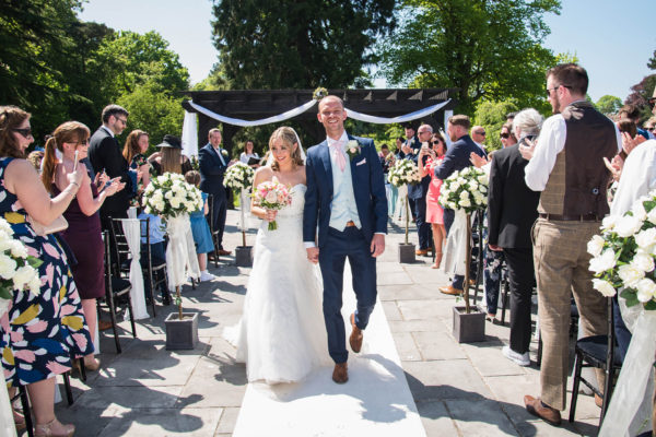 The bride and groom celebrate after their outdoor wedding ceremony at Swynford Manor