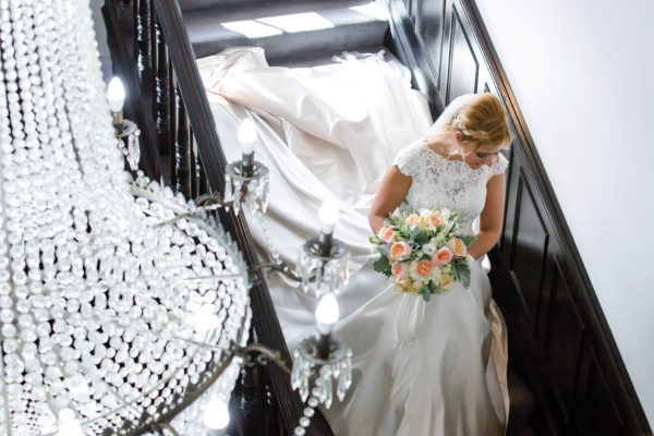 A bride holds her wedding bouquet as she walks down the grand staircase at Swynford Manor