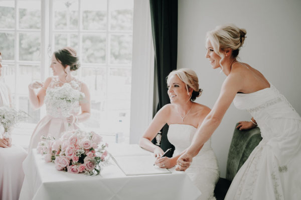Brides sign the wedding register during their wedding ceremony at Swynford Manor in Cambridgeshire