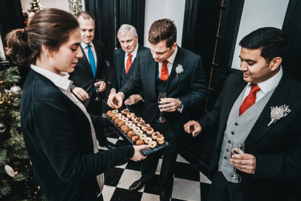 Guests help themselves to canapes during a winter wedding reception at Swynford Manor