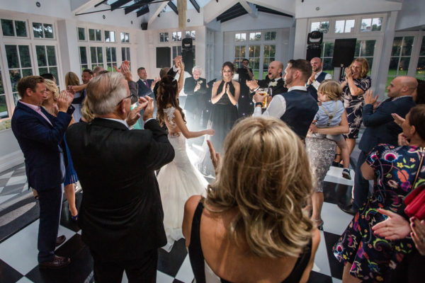 The newlyweds are surrounded by their guests as they perform their first dance in The Garden Room at Swynford Manor