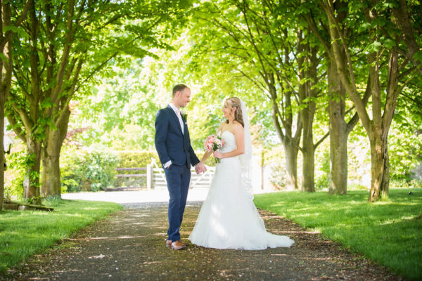 Newlyweds walk up the grand driveway at Swynford Manor wedding venue in Cambridgeshire