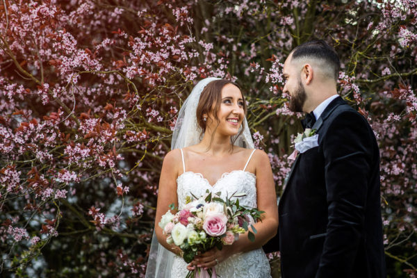 Newlyweds stand in front of a blossom tree at Swynford Manor for a beautiful spring wedding photo