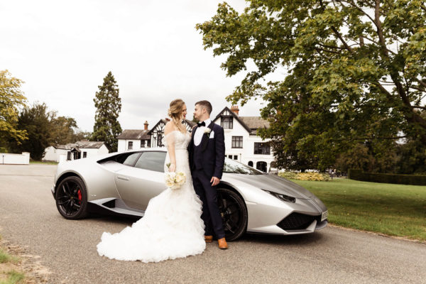 Newlyweds stand in front of a sporty wedding car on the grand driveway at Swynford Manor