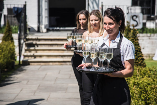 Waitresses hold trays of champagne ready for an outdoor drinks reception at Swynford Manor