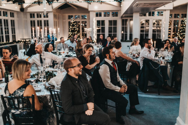 Wedding guests enjoy the speeches during a winter wedding reception at Swynford Manor