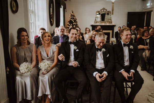 The wedding party laugh during a wedding ceremony at Swynford Manor